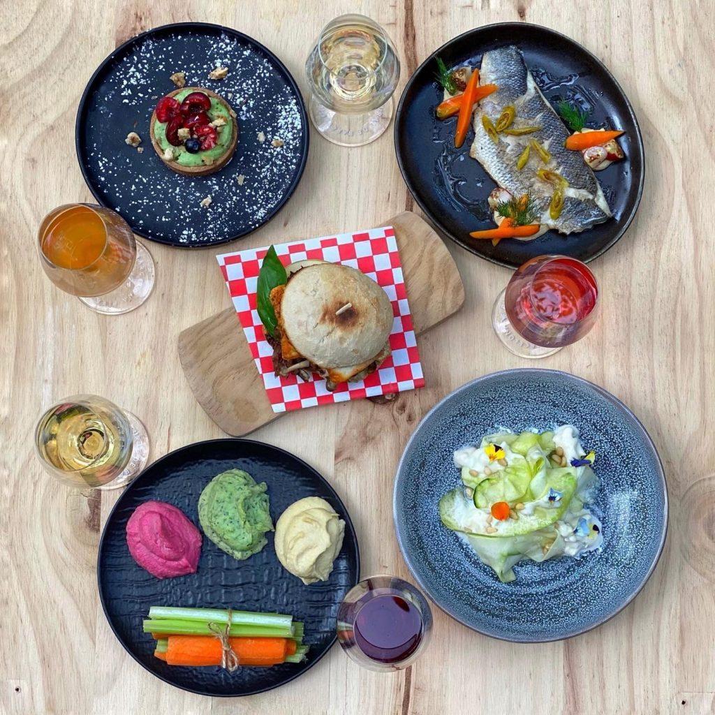 Carta de comidas y tapas de proximidad. Foto de varios platos y copas de vino alrededor