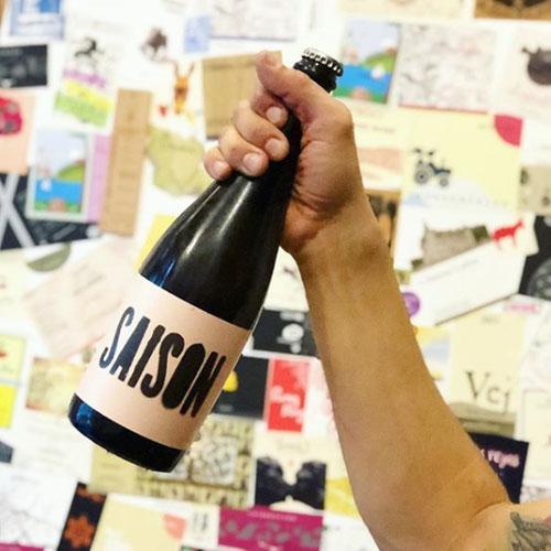 Flyer publicitario con la fotografía de una mano alzando un vino de etiqueta Saison