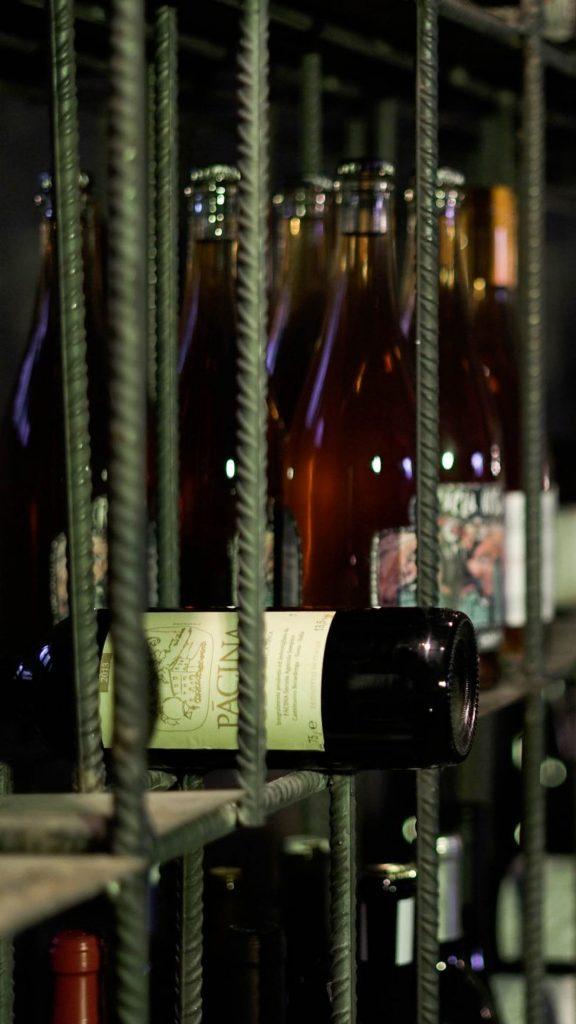 Fotografía de cerca de la enoteca mostrando diferentes etiquetas de vinos naturales en Garage Bar
