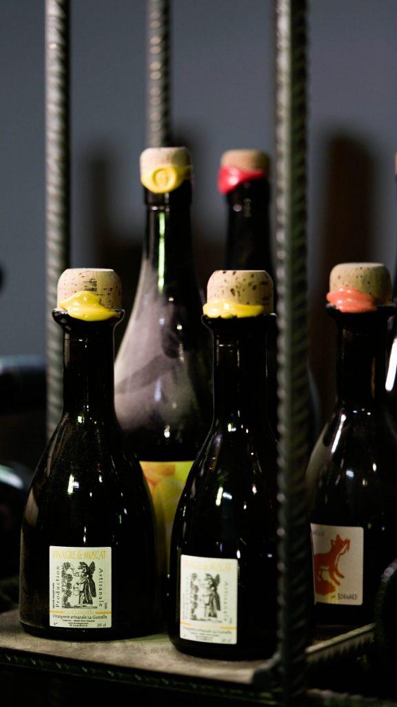 Garage Bar de vinos naturales. Fotografía de cerca de pequeñas botellas de vino en una estantería